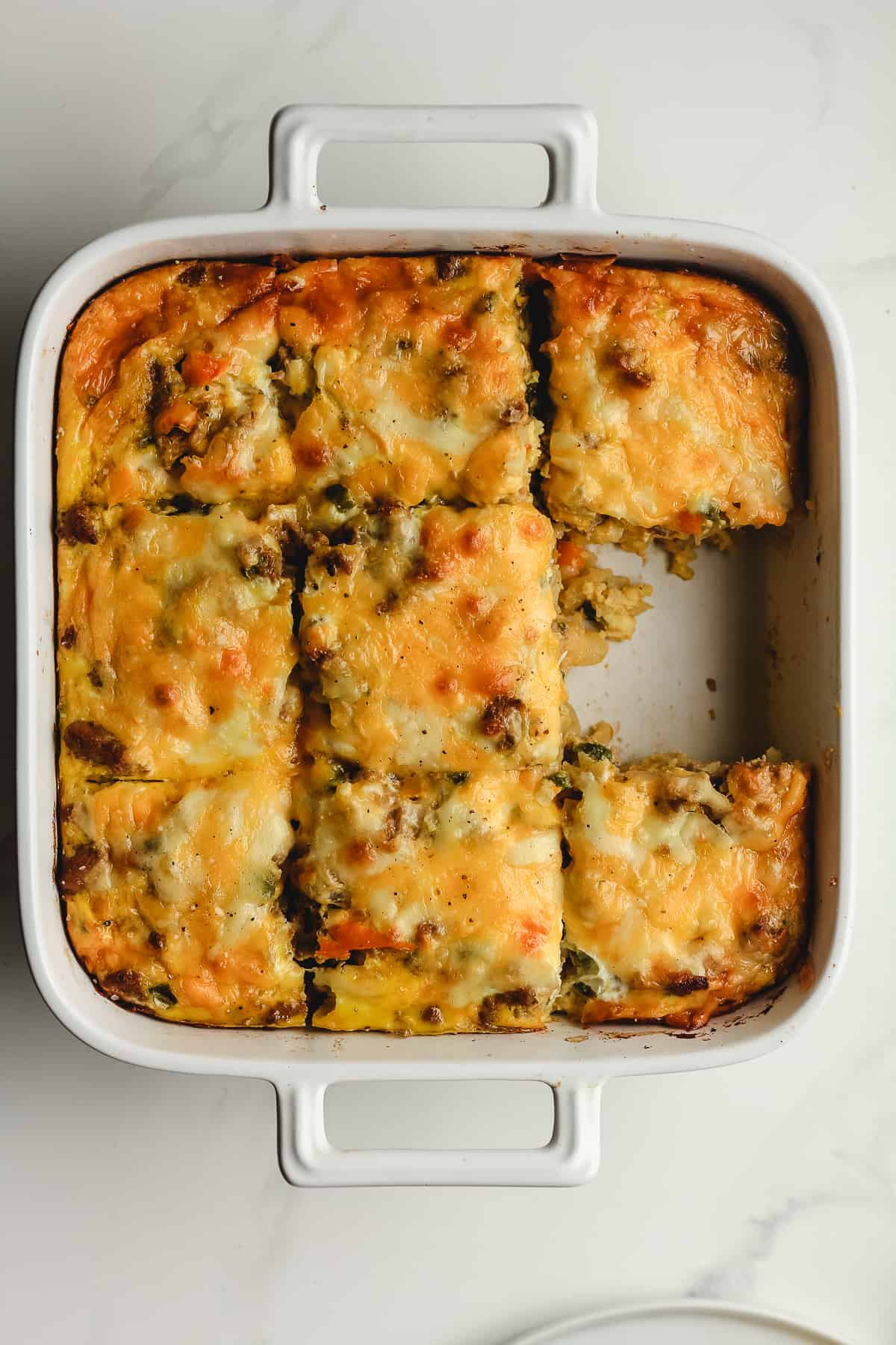 Overhead shot of a white casserole of breakfast casserole, cut into 9 squares.