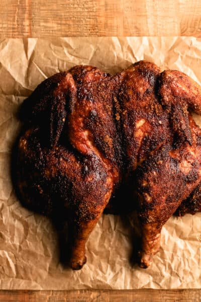 A whole smoked spatchcock chicken on parchment paper.