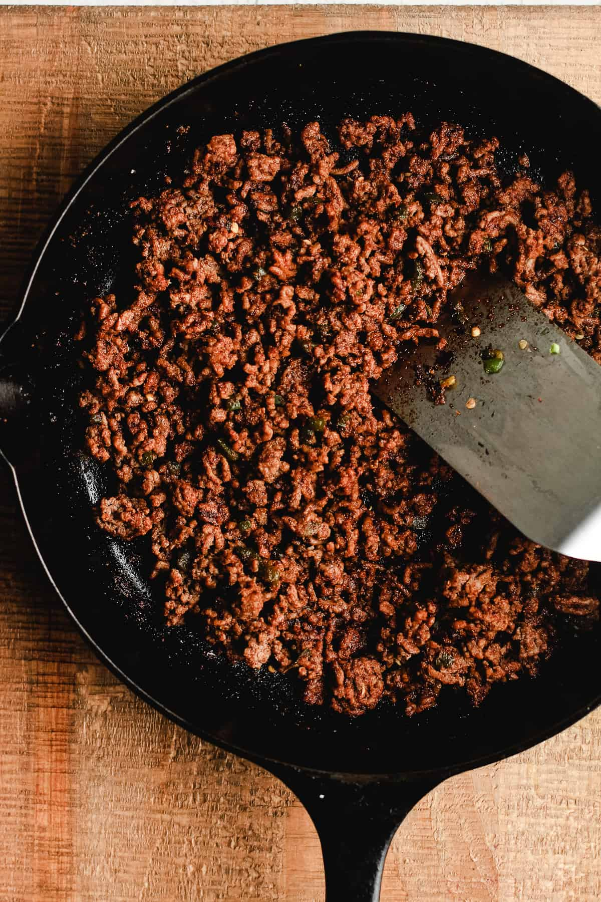 Cast iron skillet with cooked taco meat.
