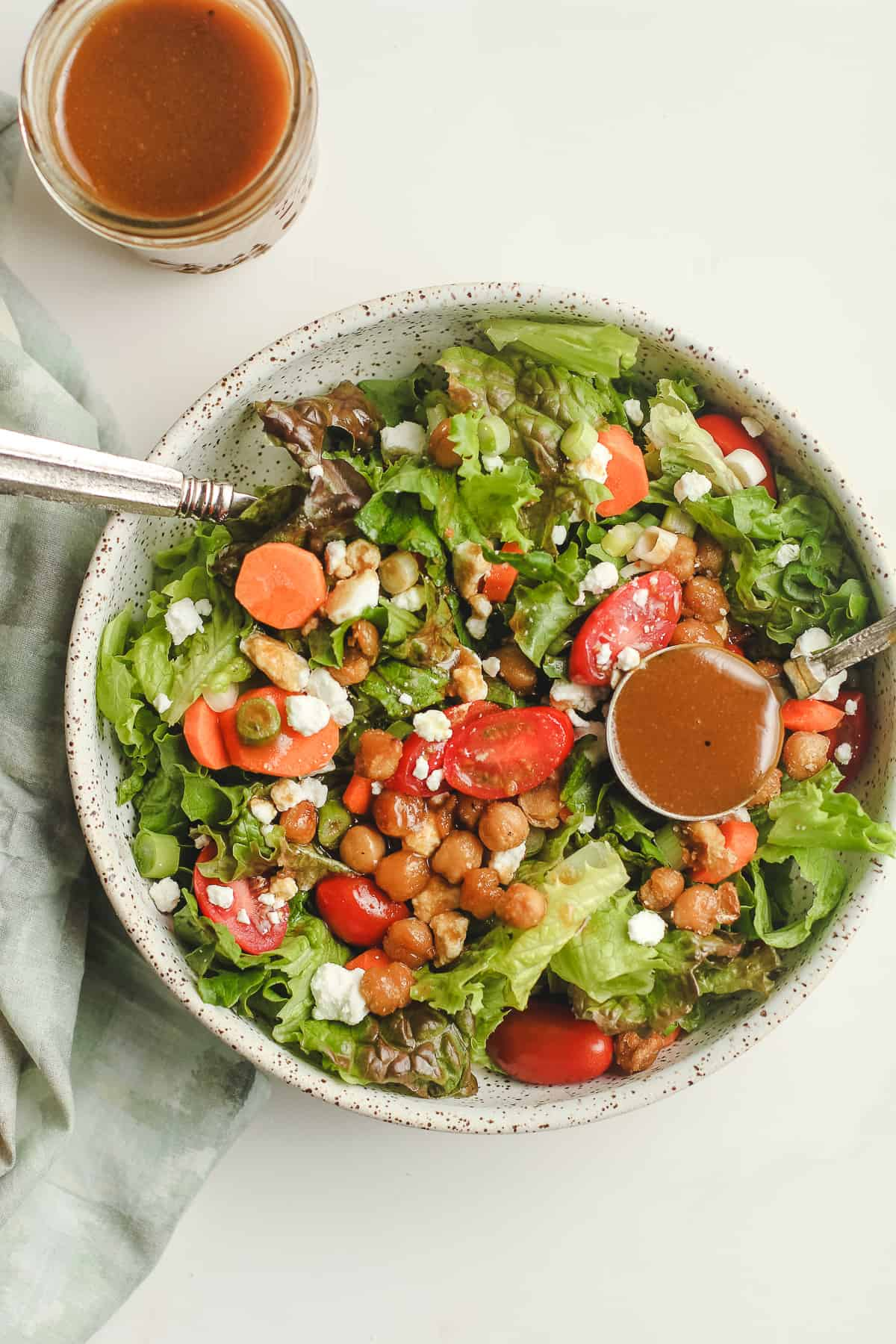 Overhead shot of a green salad with a spoonful of balsamic vinaigrette and a jar of dressing.