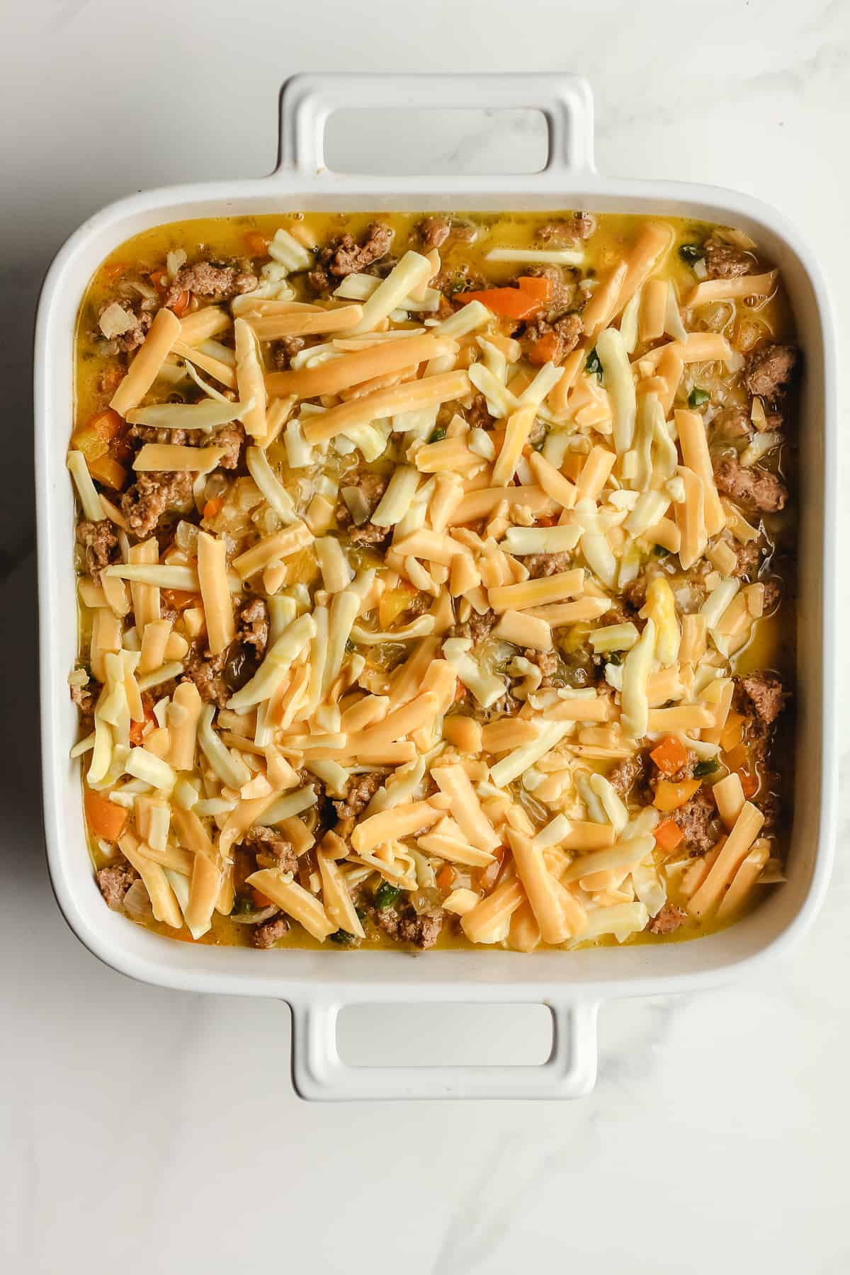 A 9 inch casserole with the unbaked casserole.