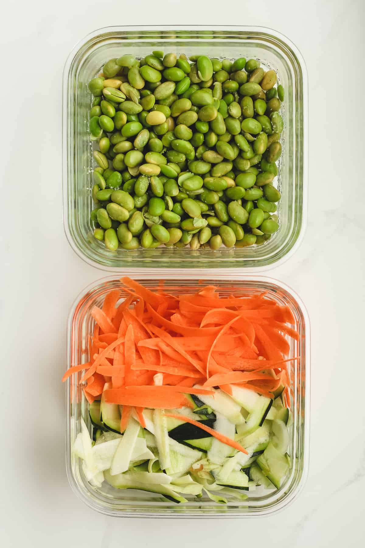 Bowls of edamame, carrots and zucchini.