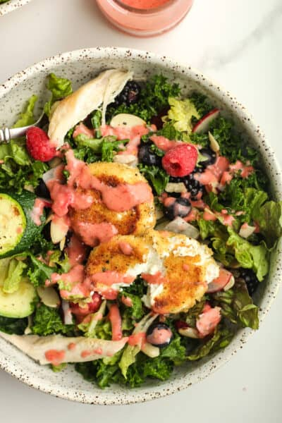 Closeup of a serving bowl of fried goat cheese salad with strawberry dressing.