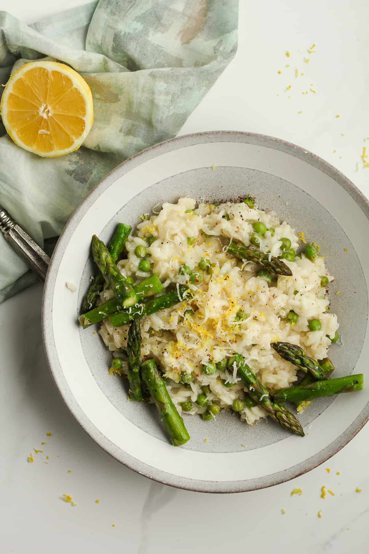 A bowl of lemon risotto with asparagus and peas.