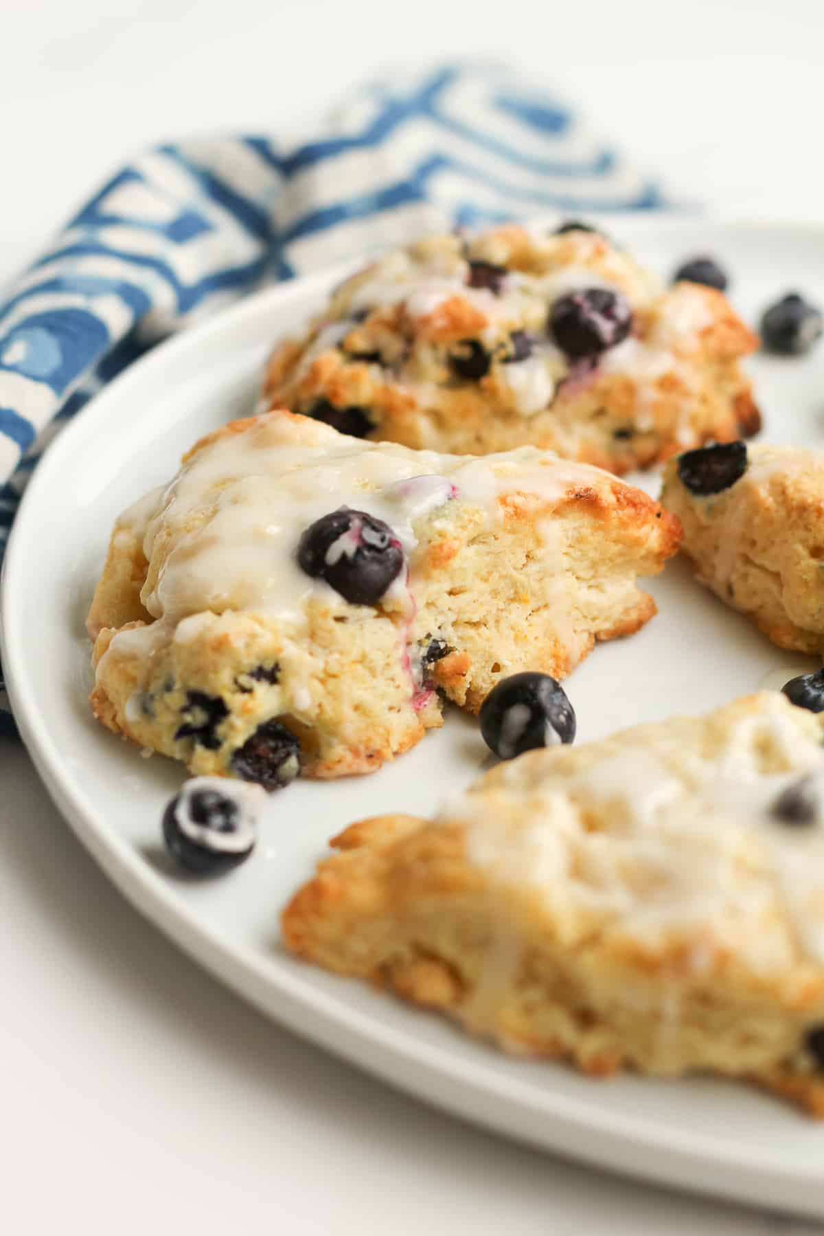 A plate of blueberry lemon scones, with a blue and white napkin.