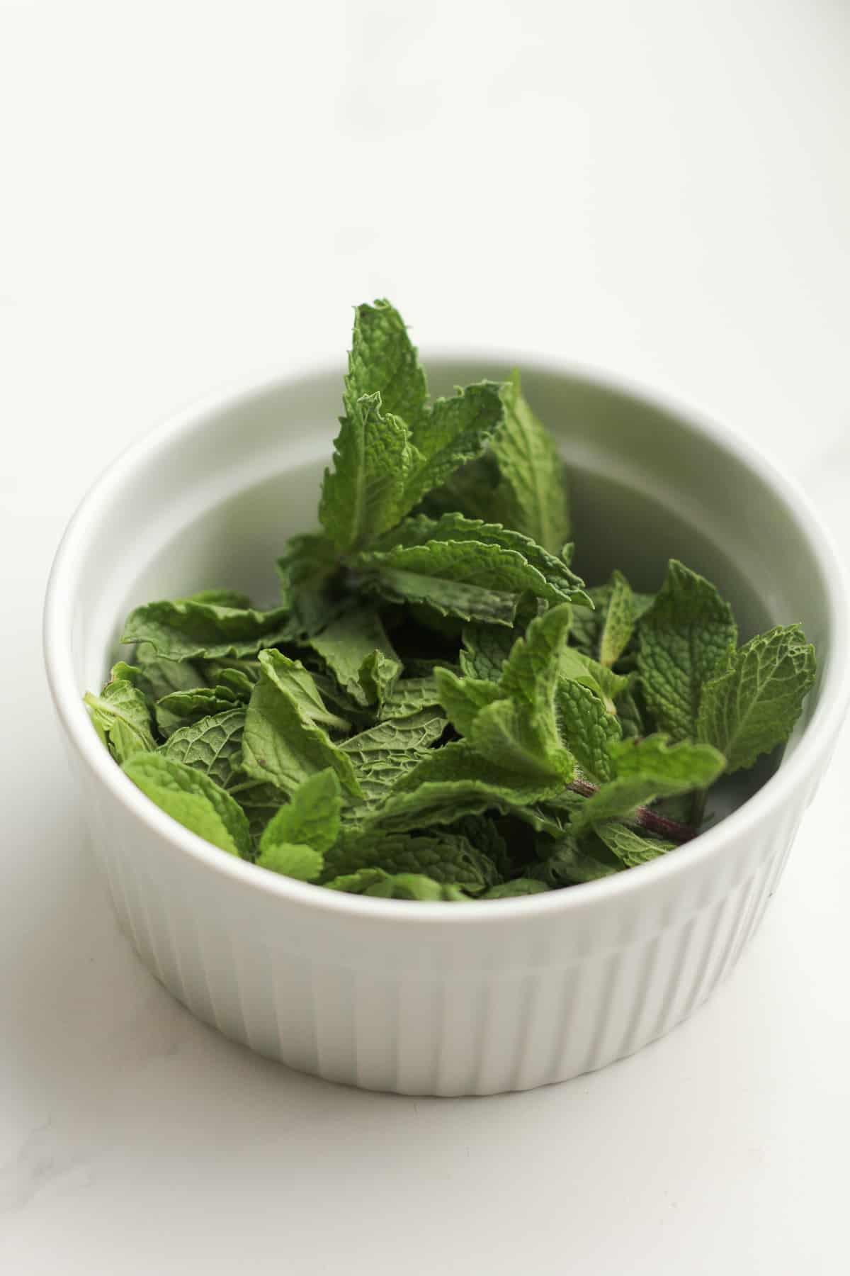 A bowl of fresh mint leaves.