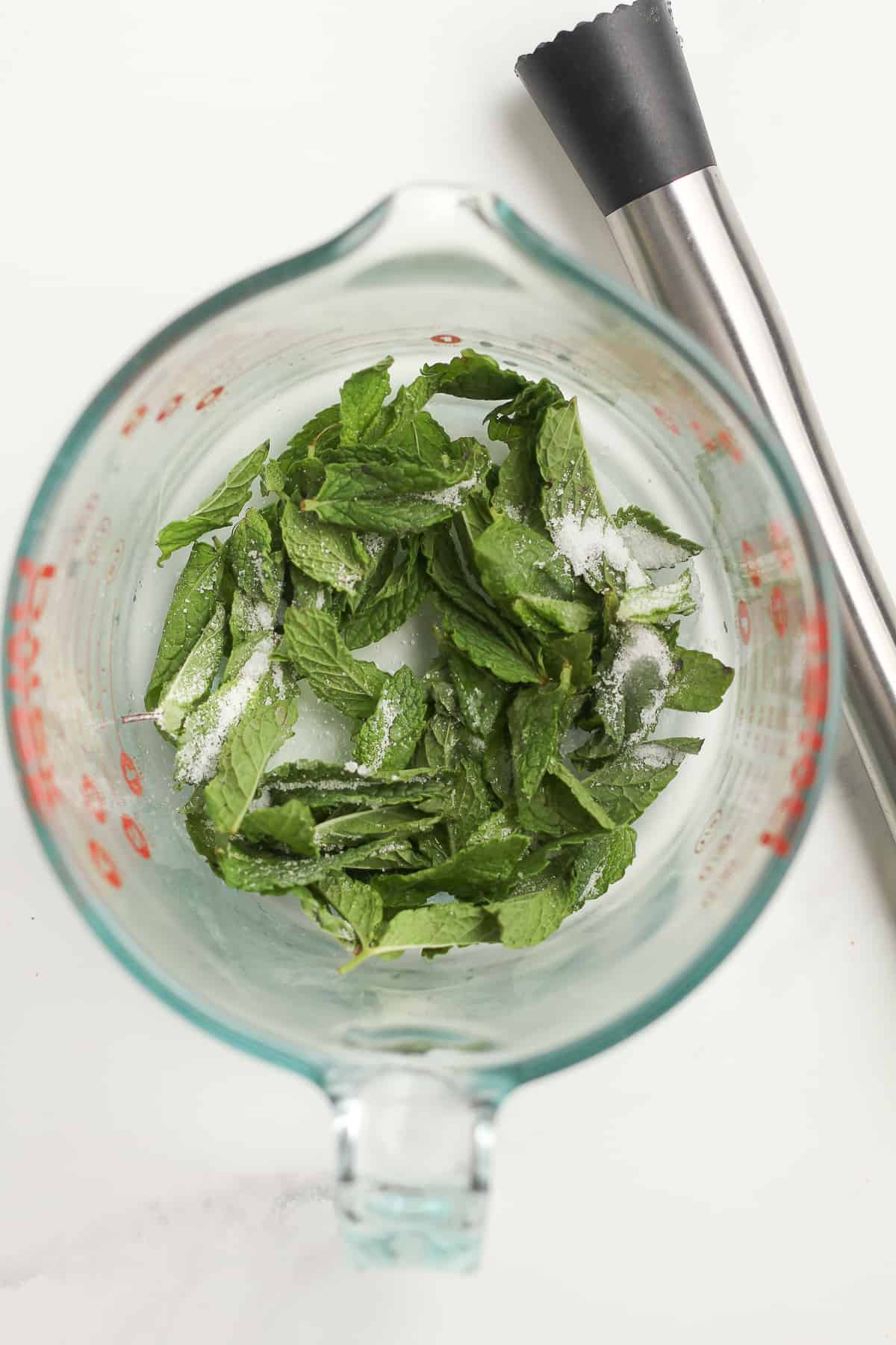A measuring cup of mint with sugar and lime juice, with a muddler.