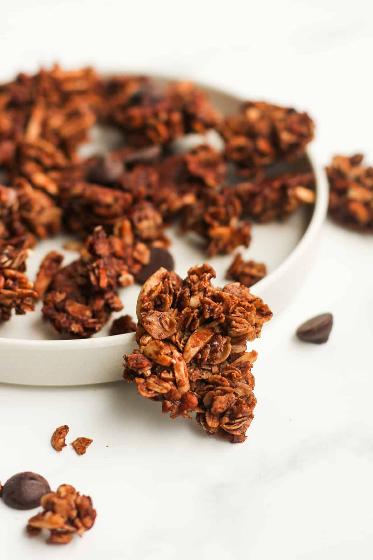 Side shot of a chocolate granola cluster by a plate.