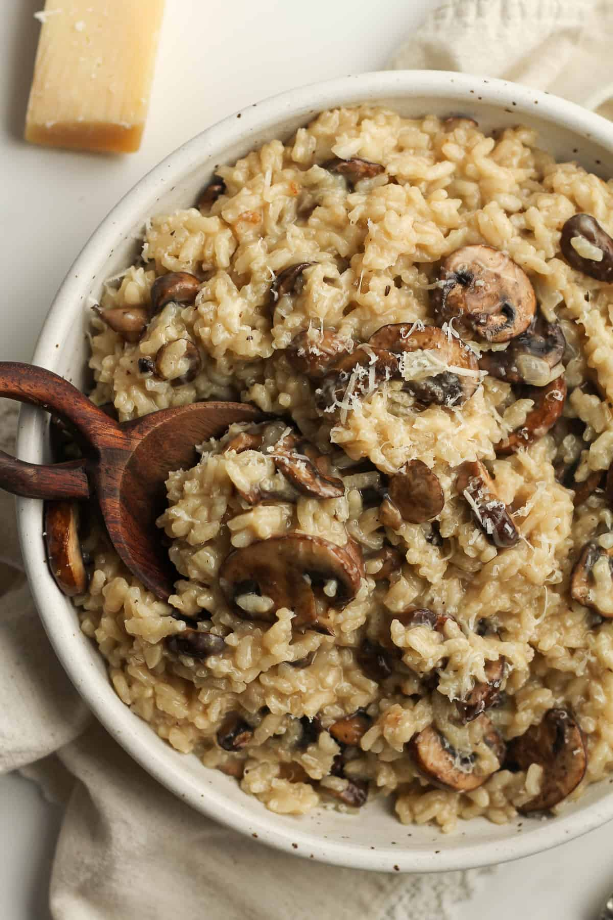 Overhead shot of a bowl of creamy mushroom risotto, with a wooden spoon.