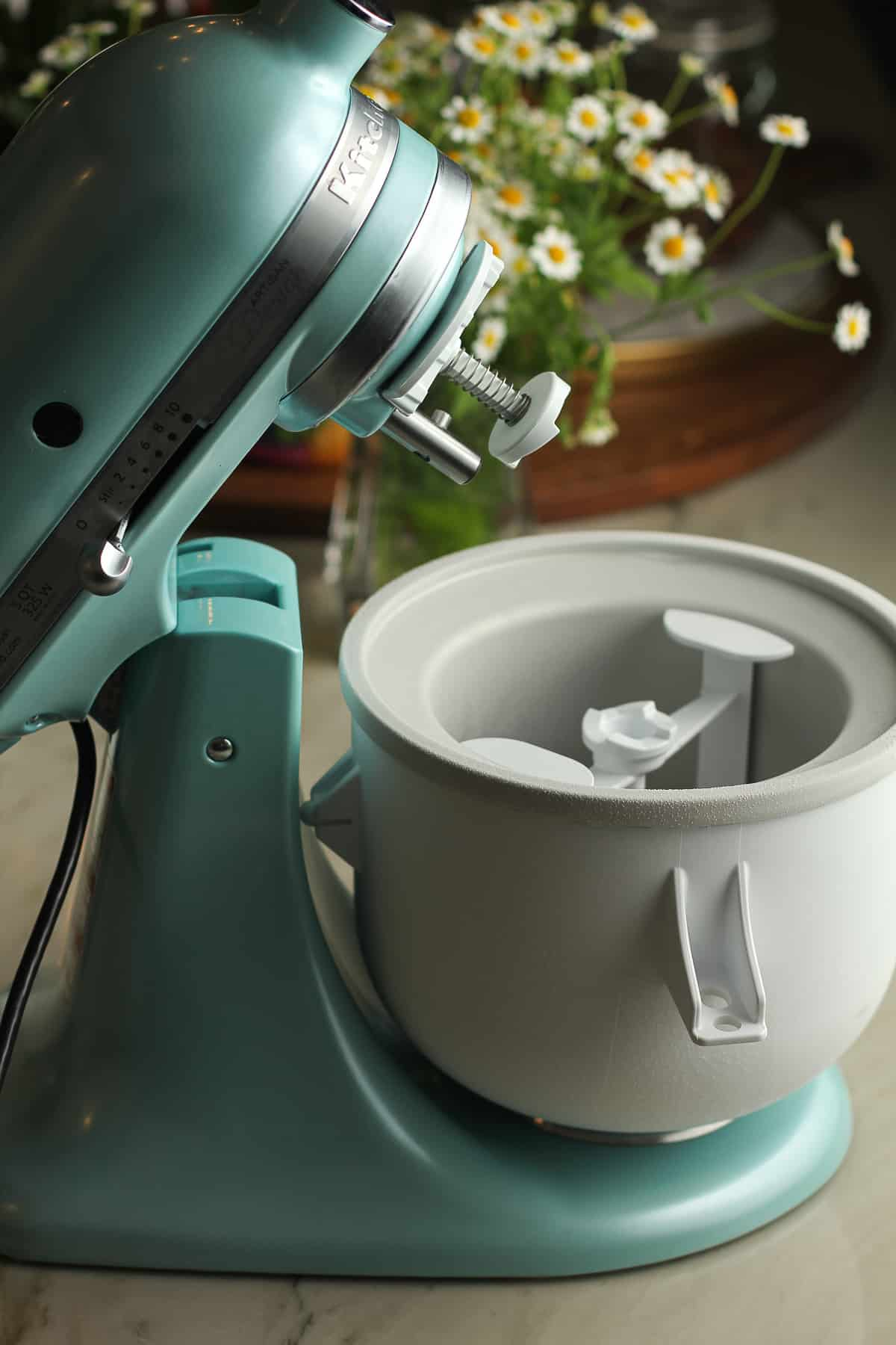 Side shot of a KitchenAid mixer with an ice cream attachment.