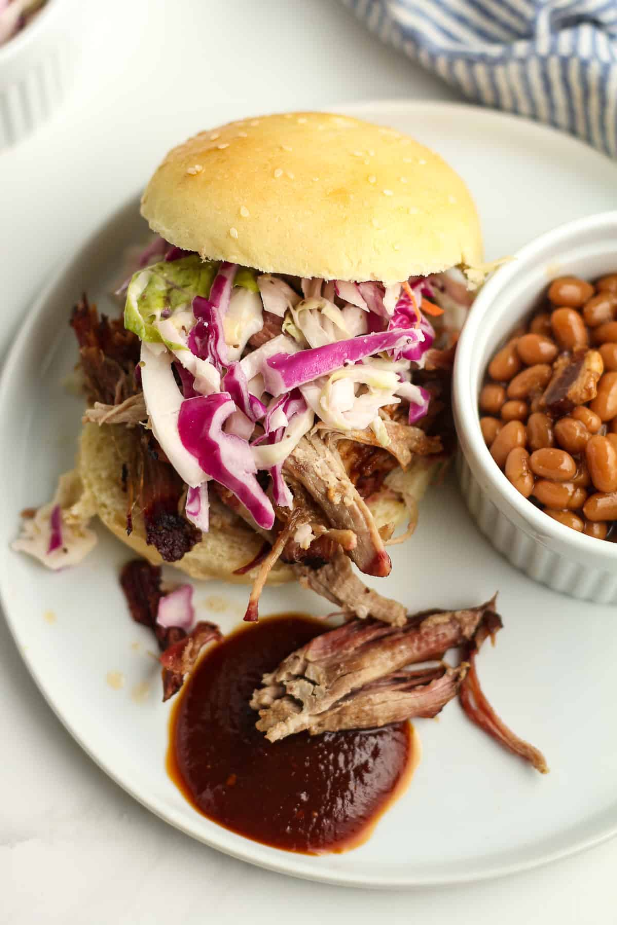 A plate with a pulled pork sandwich, with coleslaw and barbecue sauce.