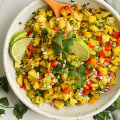 A bowl of pineapple salsa, with lime wedges.