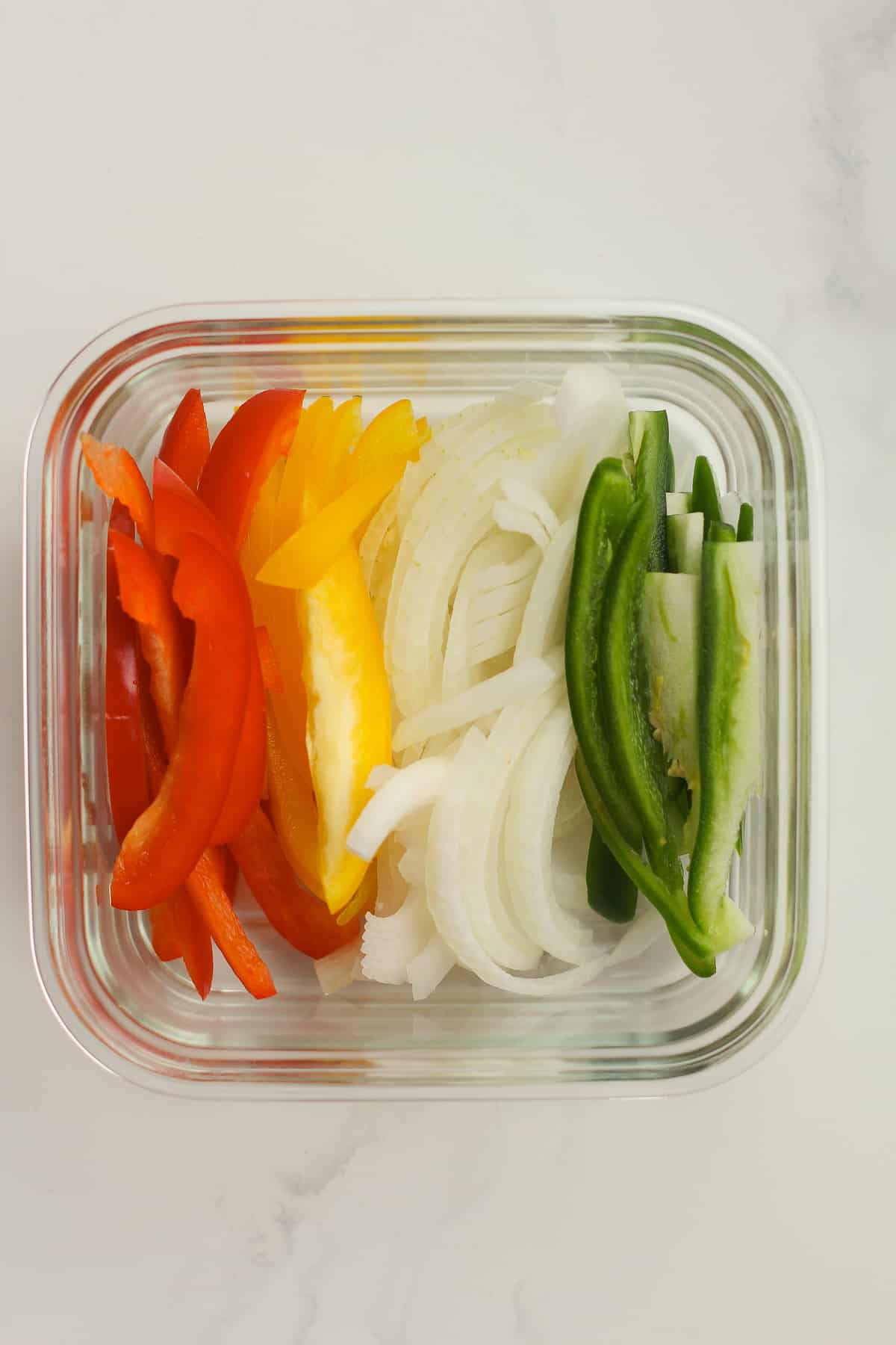 Sliced peppers and onions in a glass bowl.