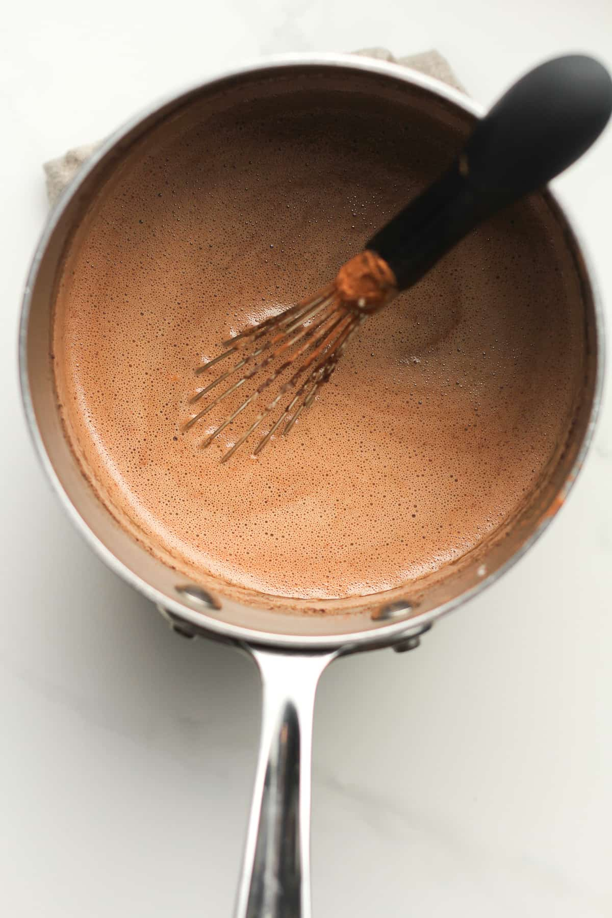 A pan of the hot tempered egg and chocolate peanut butter mixture with a whisk.