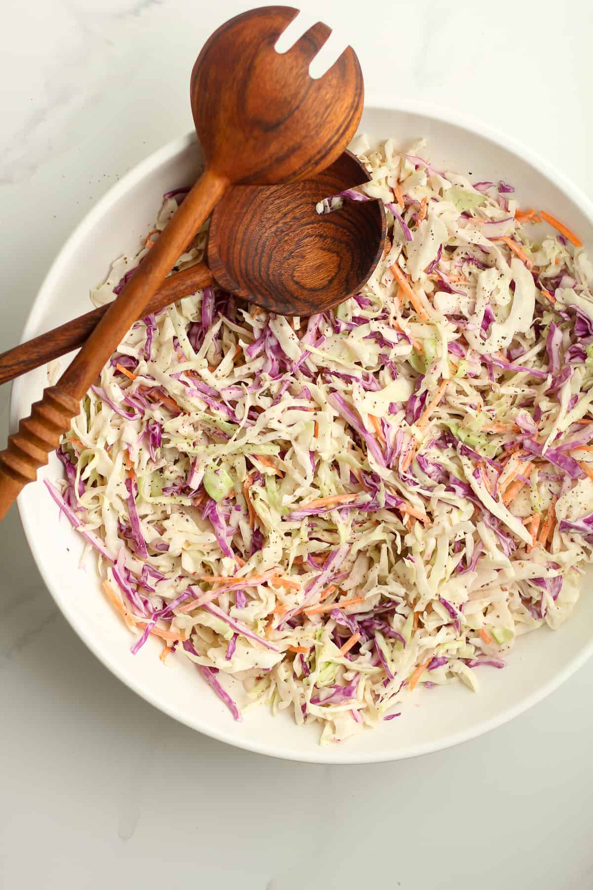 A large white bowl of creamy coleslaw with two spoons.
