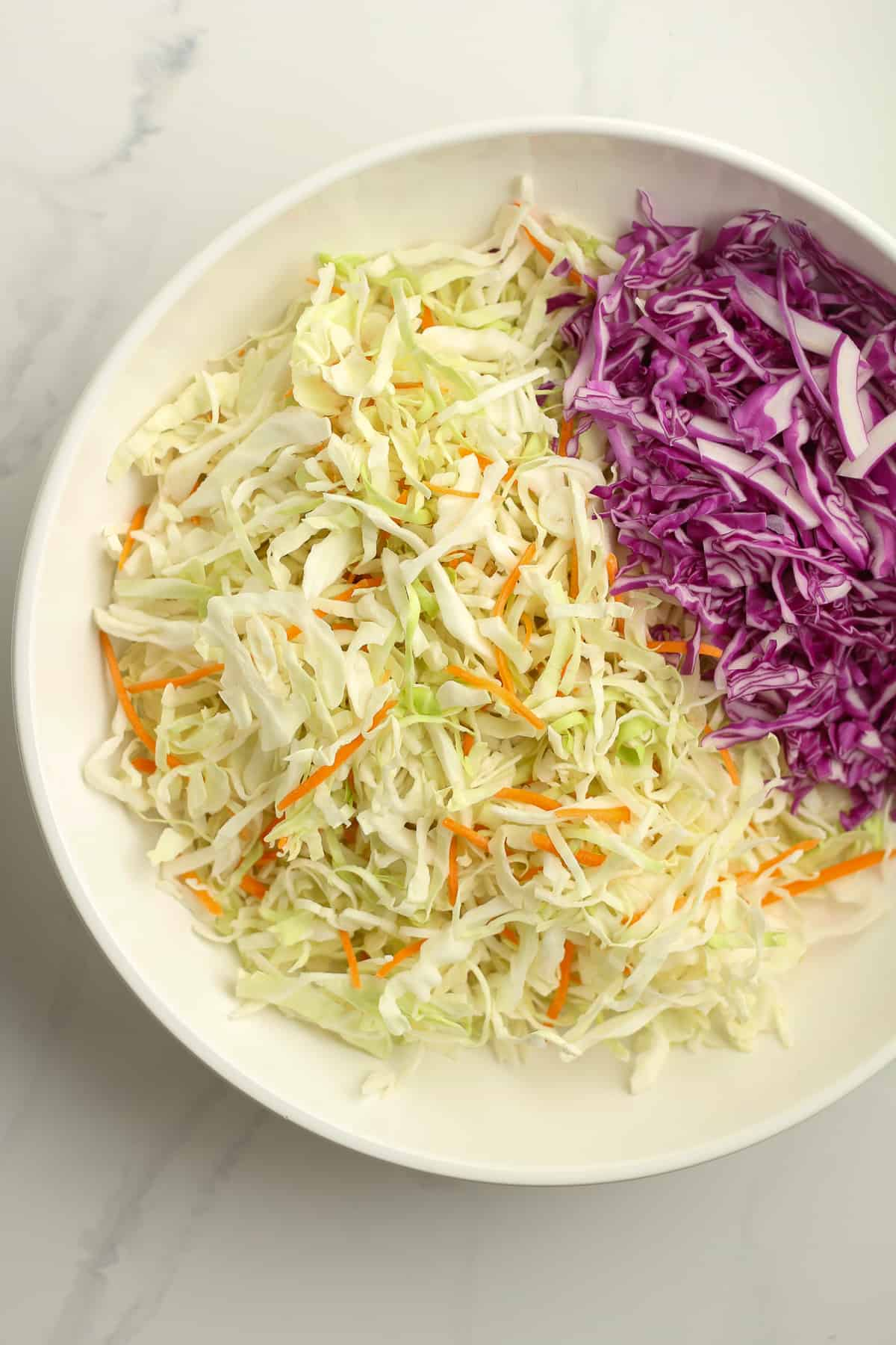 A bowl of cabbage slaw and red cabbage.