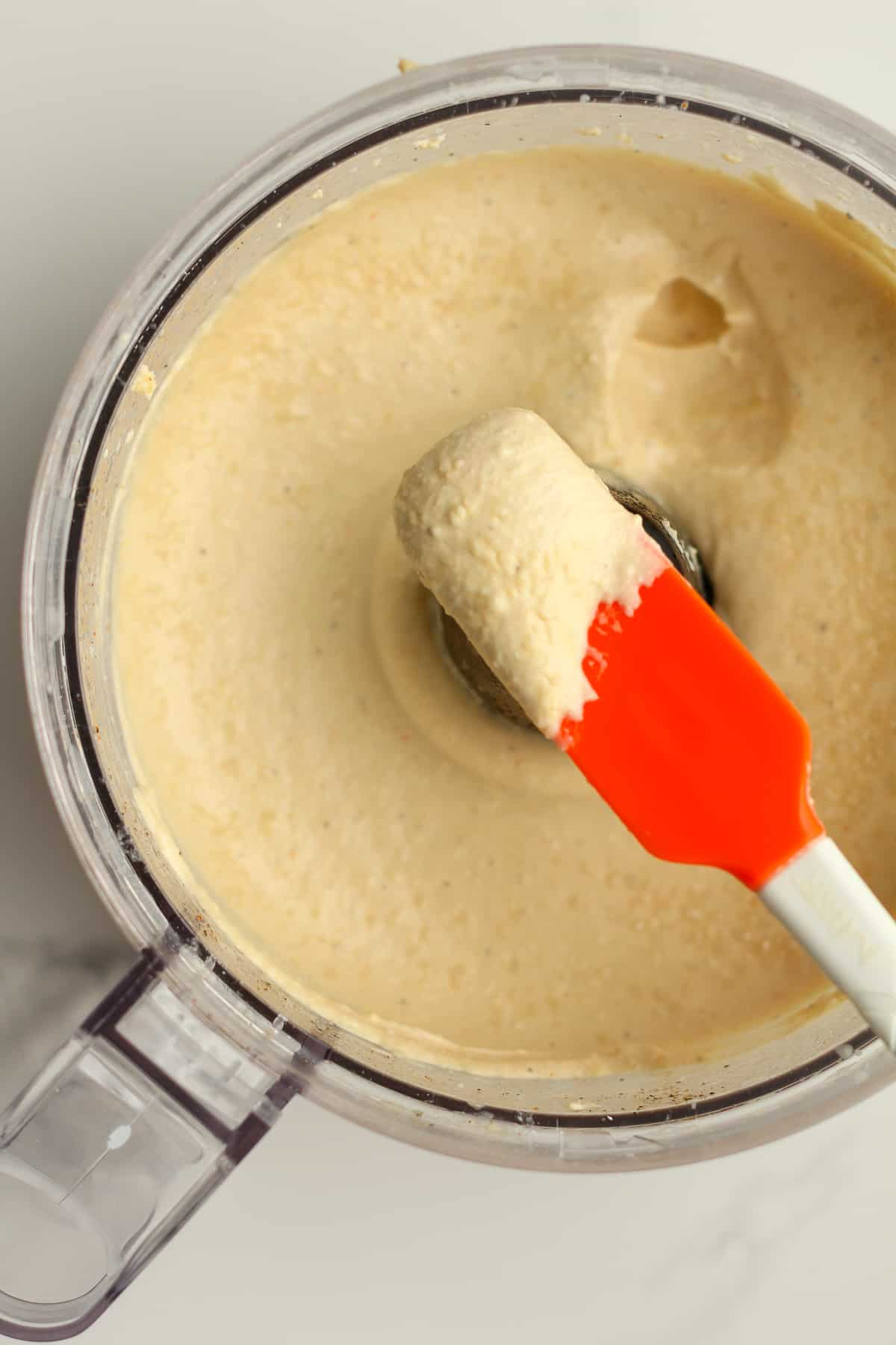 A spatula showing how creamy the hummus is.