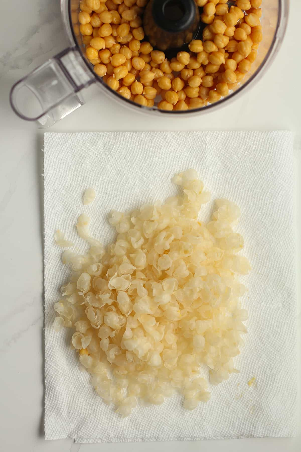 Overhead shot of some chickpea skins next to a food processor of chickpeas.