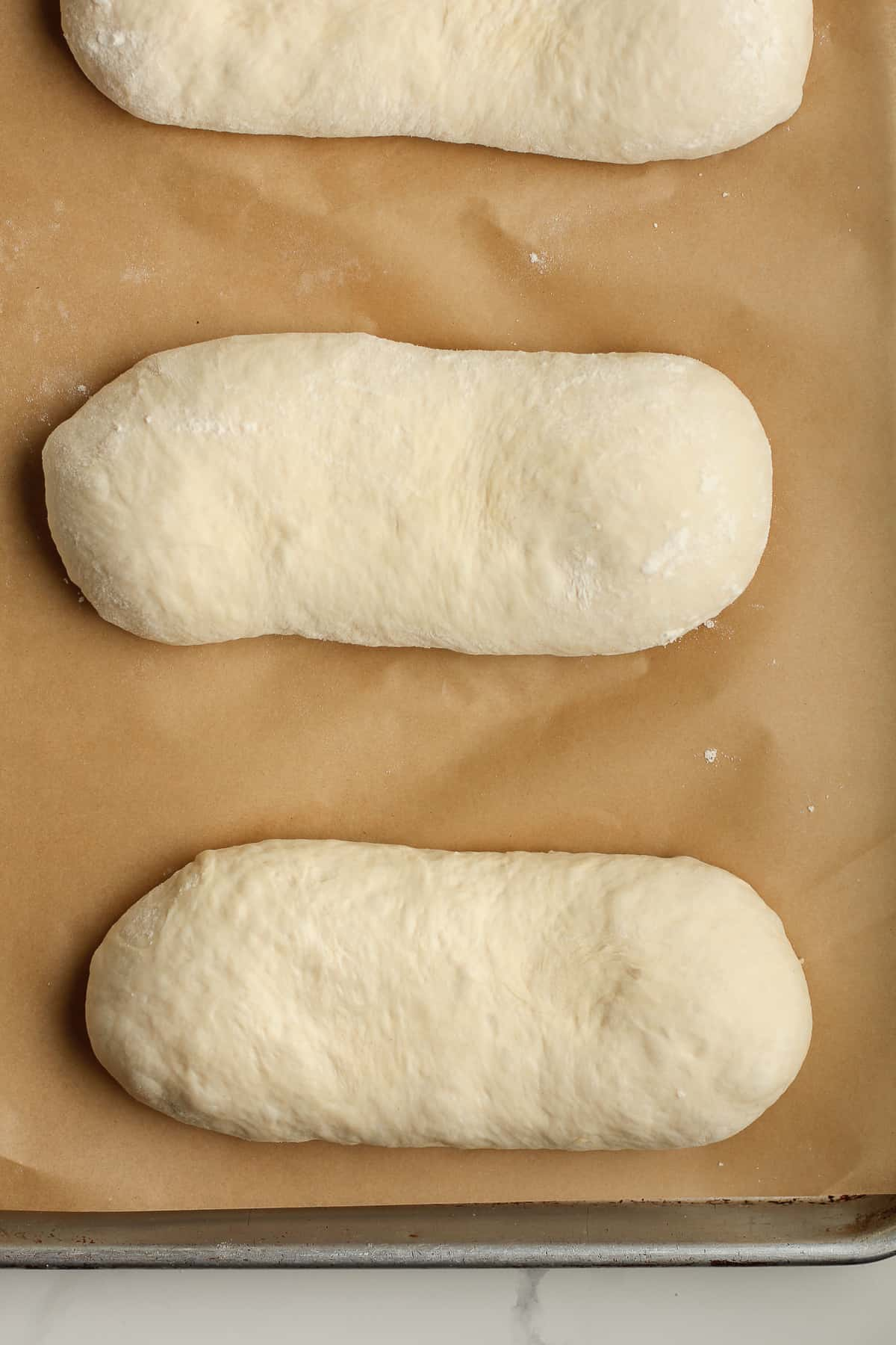 Overhead shot of small French bread dough shapes.