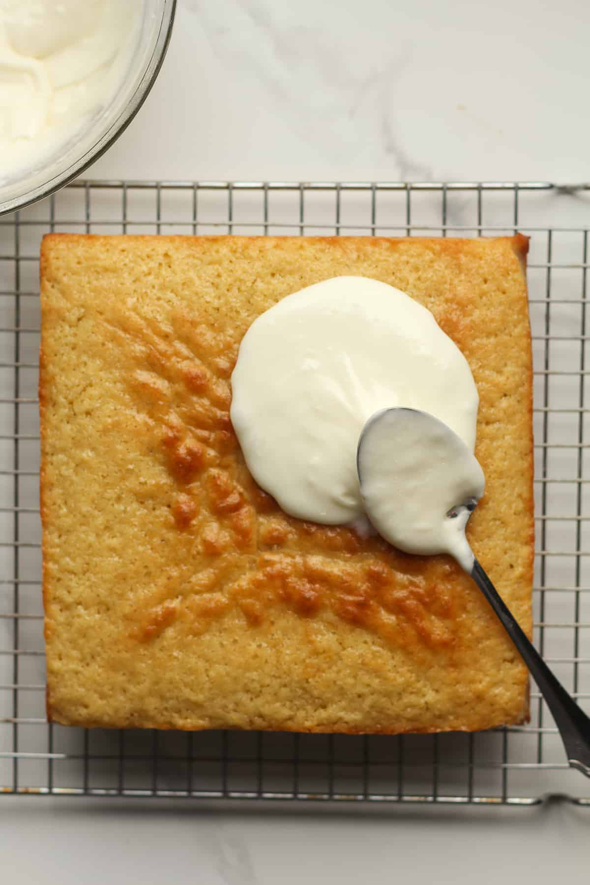 A square lemon cake with some of the frosting on top.