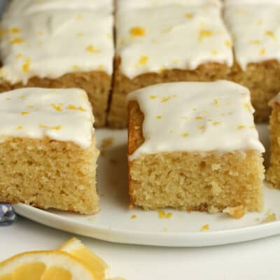 Side shot of a plate of lemon cake, cut into pieces.