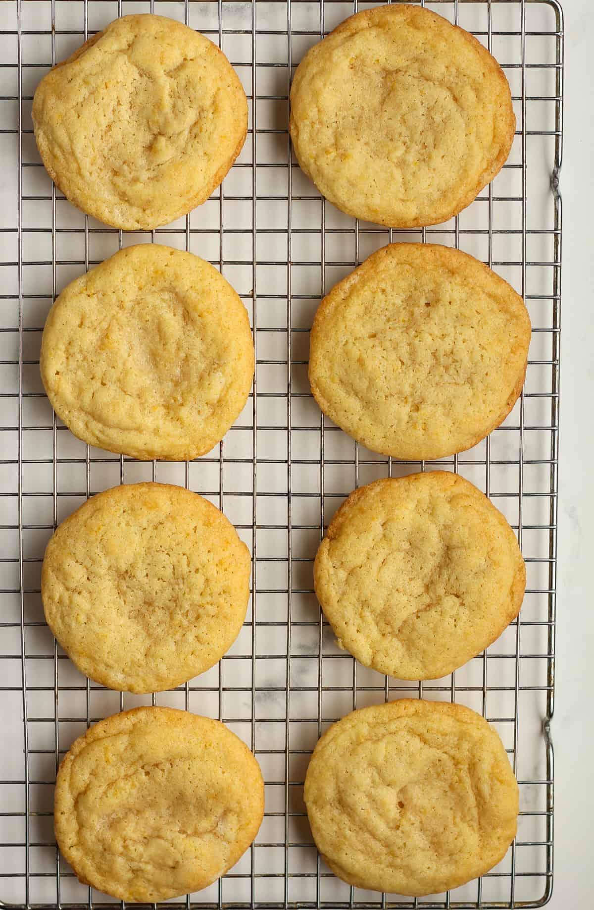 Eight just baked lemons sugar cookies on a cooling rack.