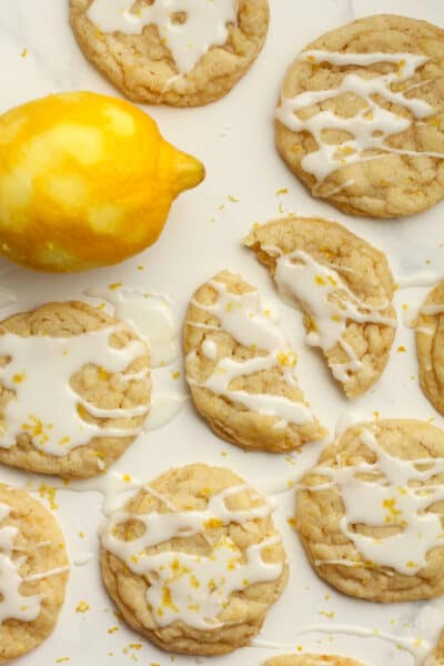 Several lemon sugar cookies with glaze, and one cookie in half.