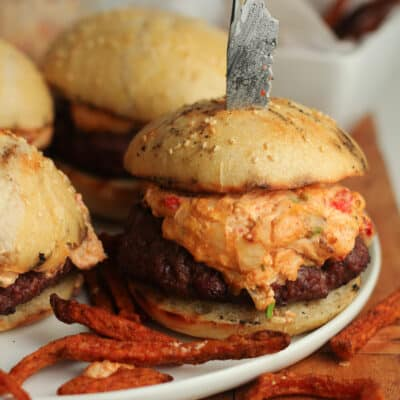 Side shot of a pimento cheese burger, with a knife in it.