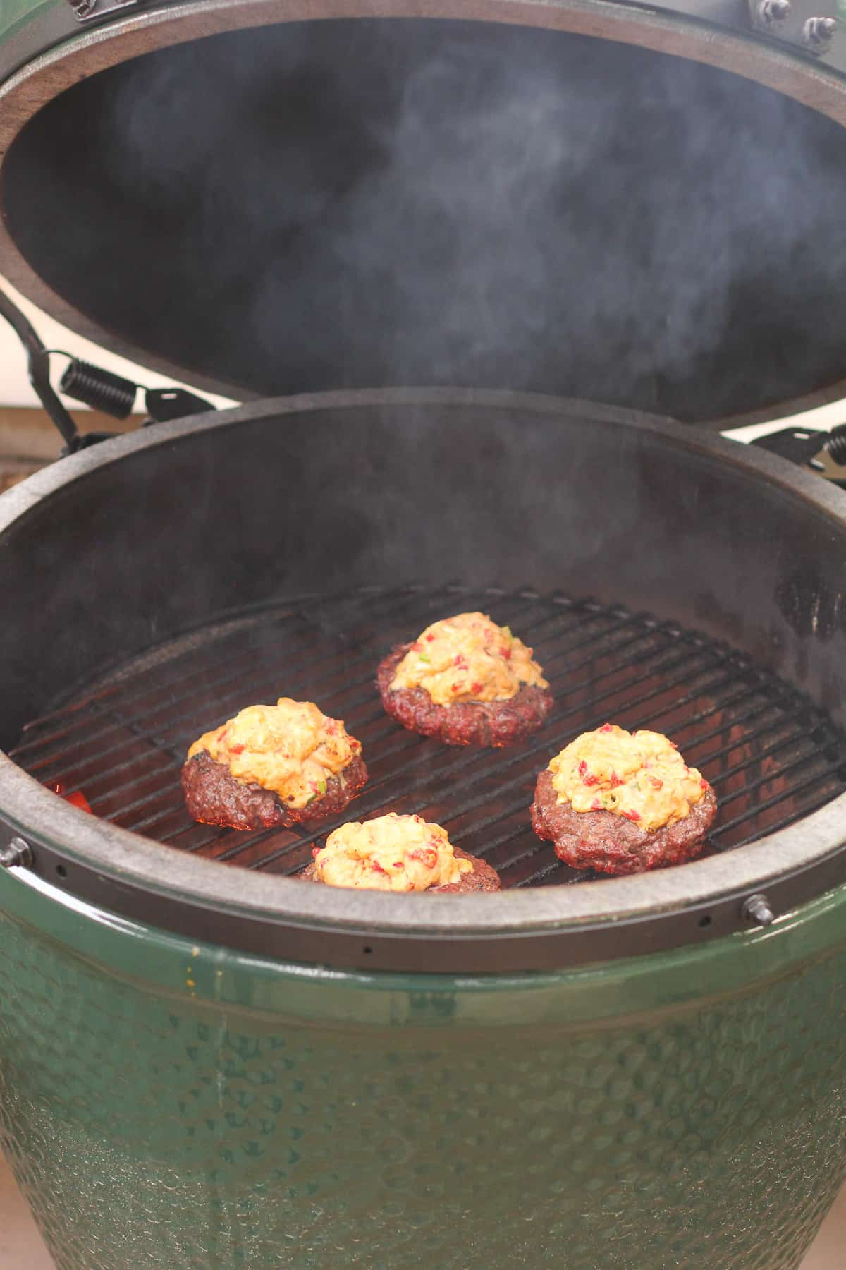 A grill with four burgers topped with pimento cheese.