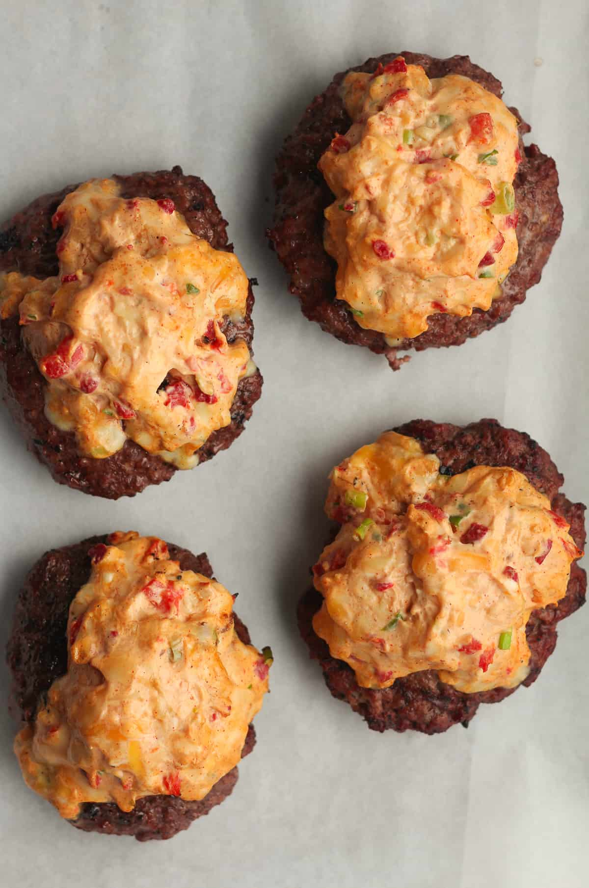 Four just grilled burgers with pimento cheese on top.
