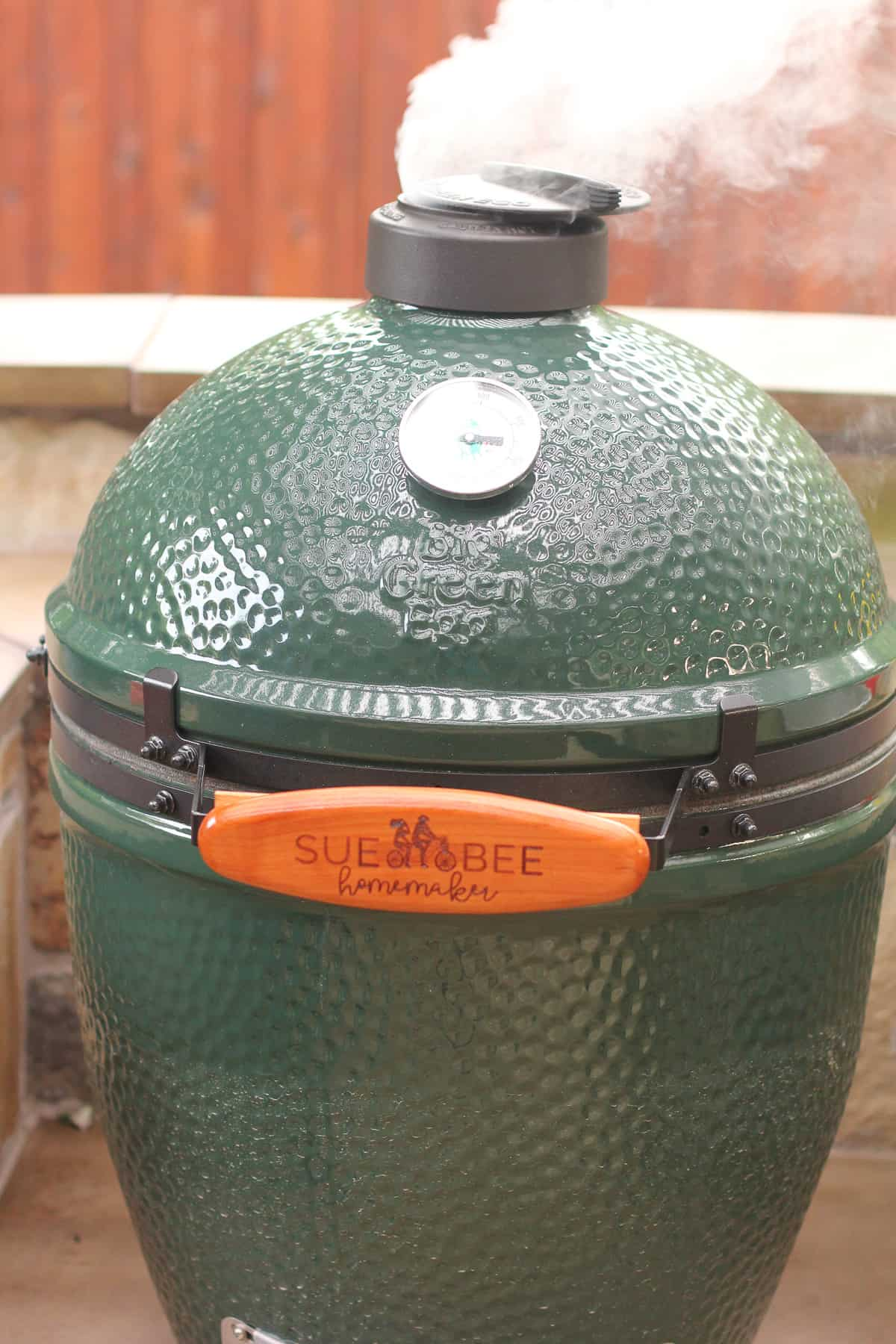 Our Big Green Egg with smoke coming out of the top.