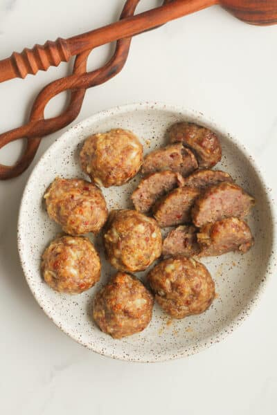 Overhead shot of a bowl of sausage meatballs, with two of them sliced.