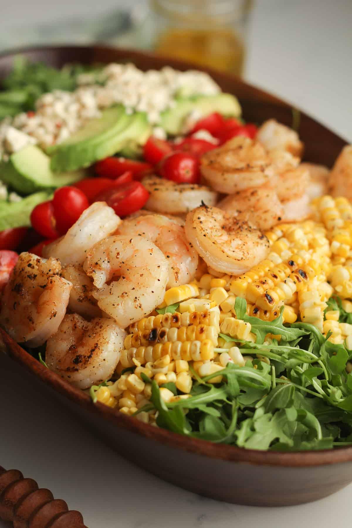 Side shot of a wooden bowl of shrimp salad.