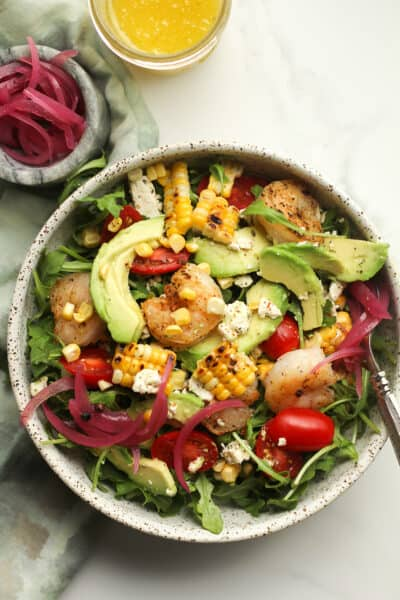 A bowl of avocado shrimp salad with grilled corn and pickled red onions.