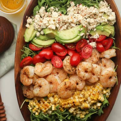 A wooden bowl of a shrimp avocado salad with feta, tomatoes, and corn.