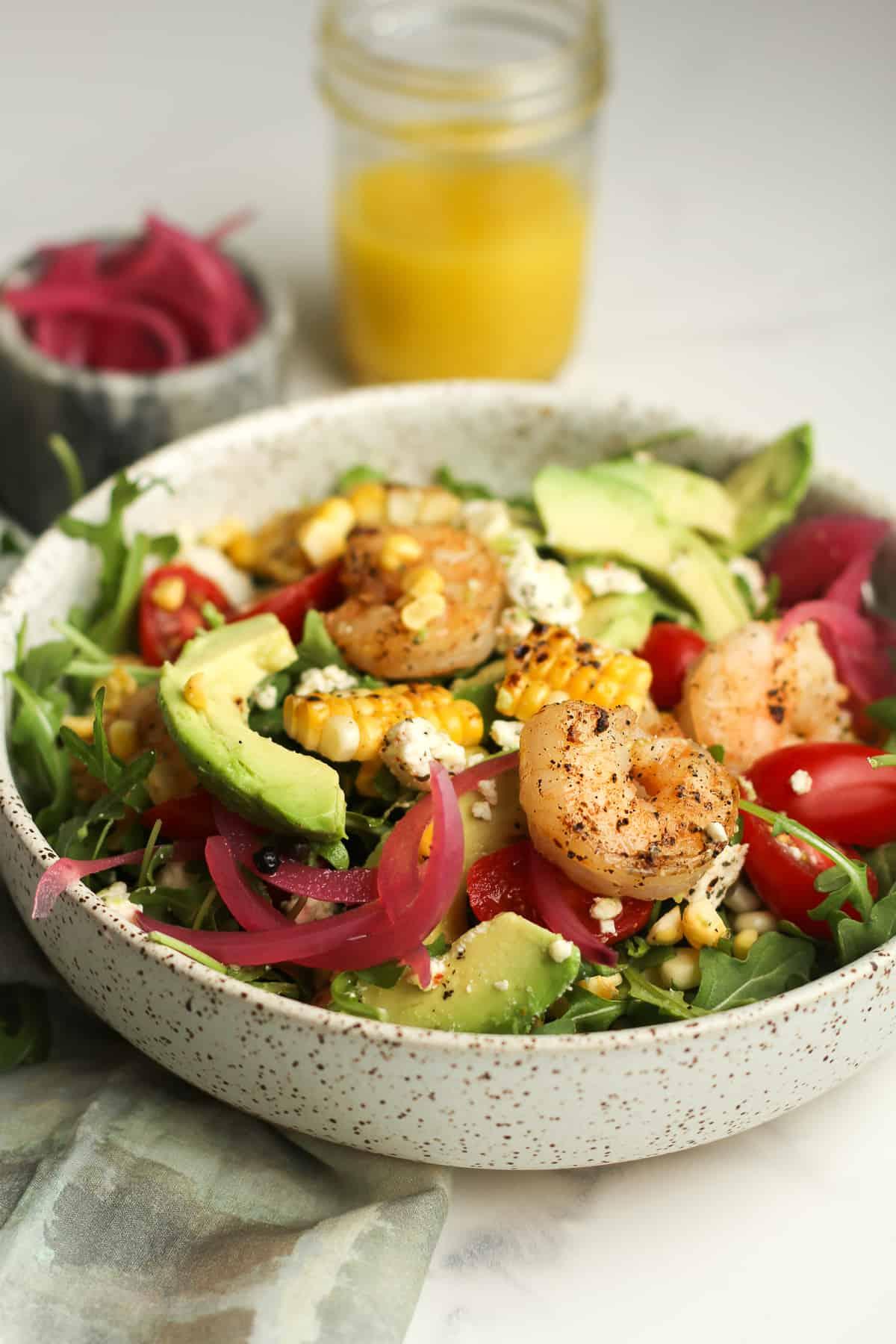 A side shot of a shrimp avocado salad with a jar of lemon dressing.