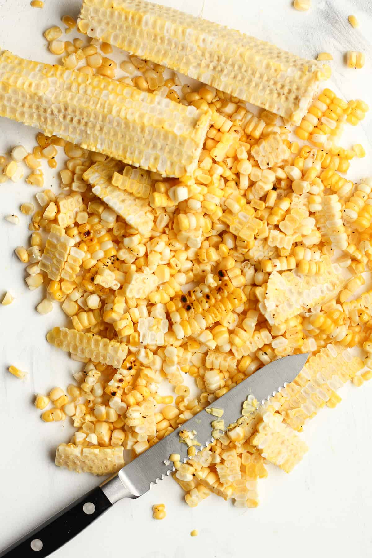 A board with the removed corn kernels next to cobs.