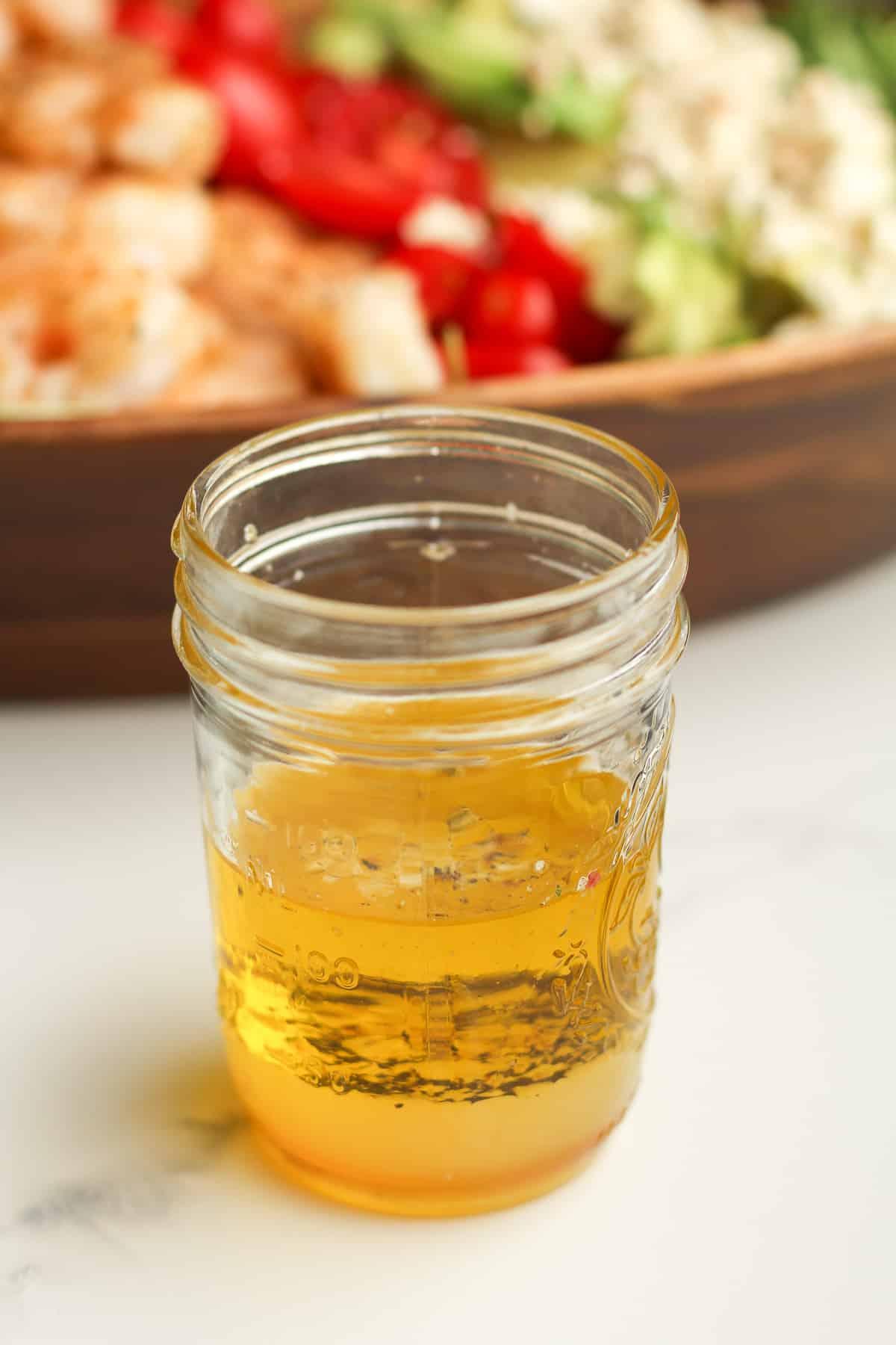 Side shot of a jar of lemon dressing.