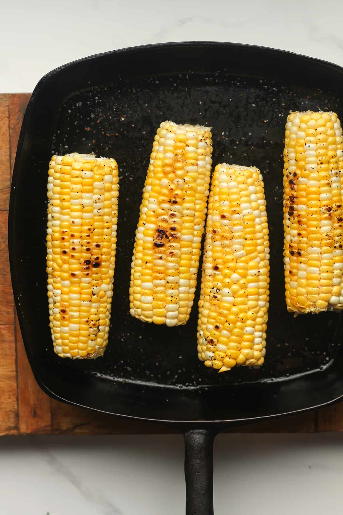 Grilled corn in a cast iron skillet.