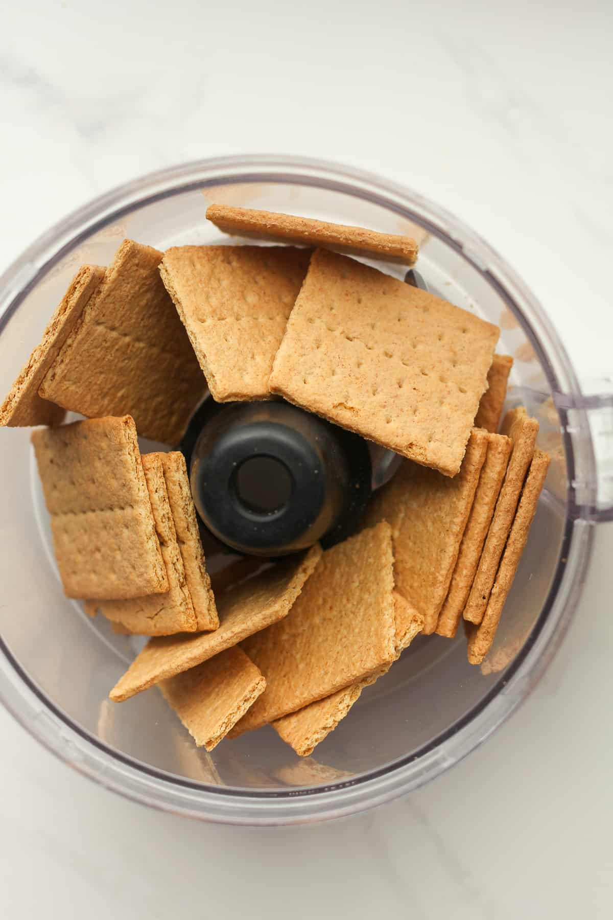 A food processor with graham crackers in it.