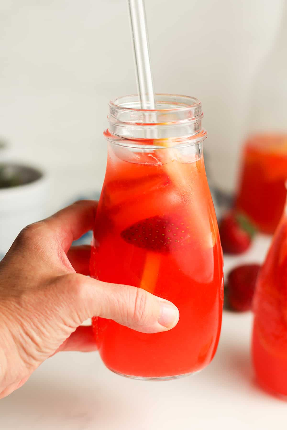 A hand holding up a strawberry lemonade with vodka.