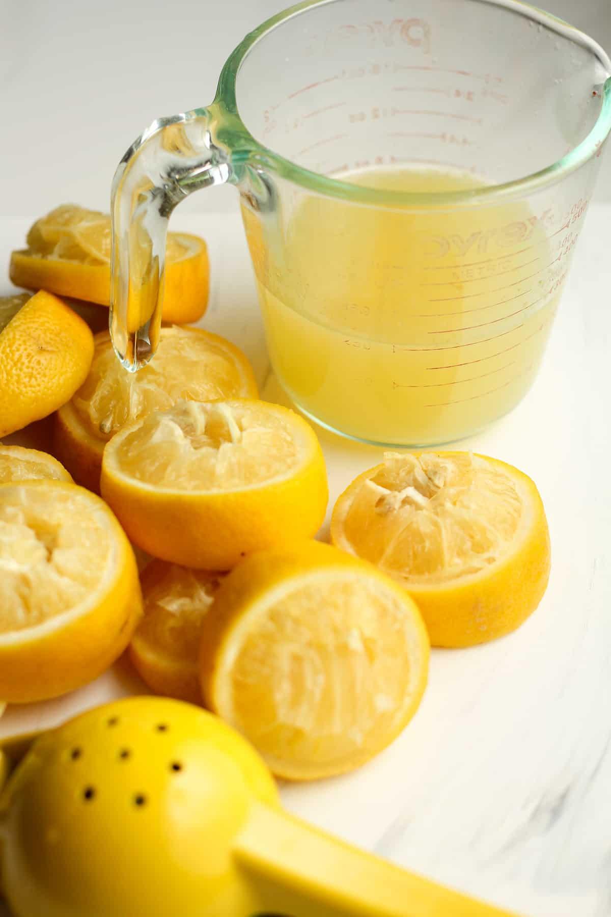 Side shot of lemon juice with 1/2 lemons just squeezed.