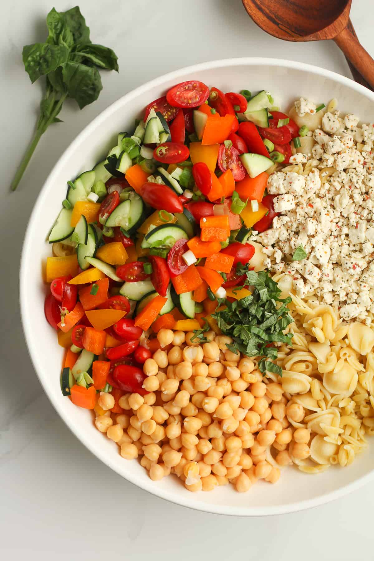 A bowl of the pasta salad ingredients, separated by ingredient.