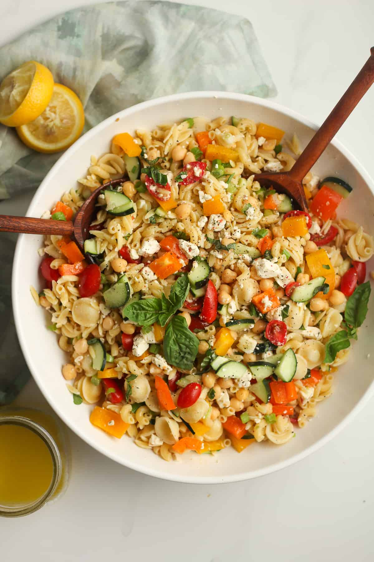 Overhead shot of a large bowl of summer pasta salad with wooden spoons.