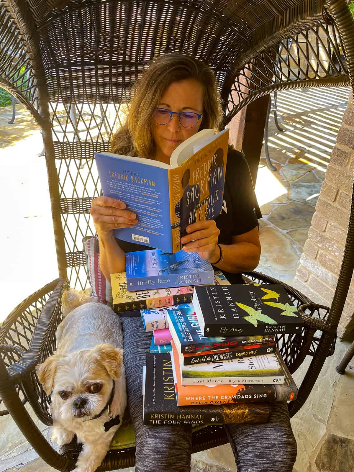 Me reading a book with a whole bunch of books on my lap, and my dog on the chair with me.