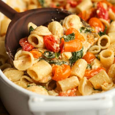 A dish of the baked feta pasta with a spoonful on top.