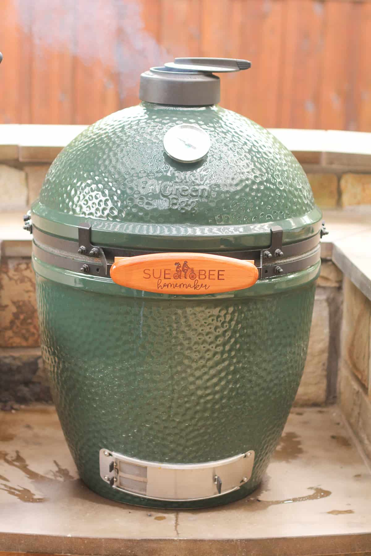 A Big Green Egg with smoke coming out of the top.