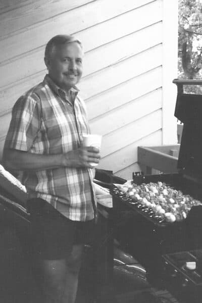 My dad grilling some kabobs with a drink in his hand.