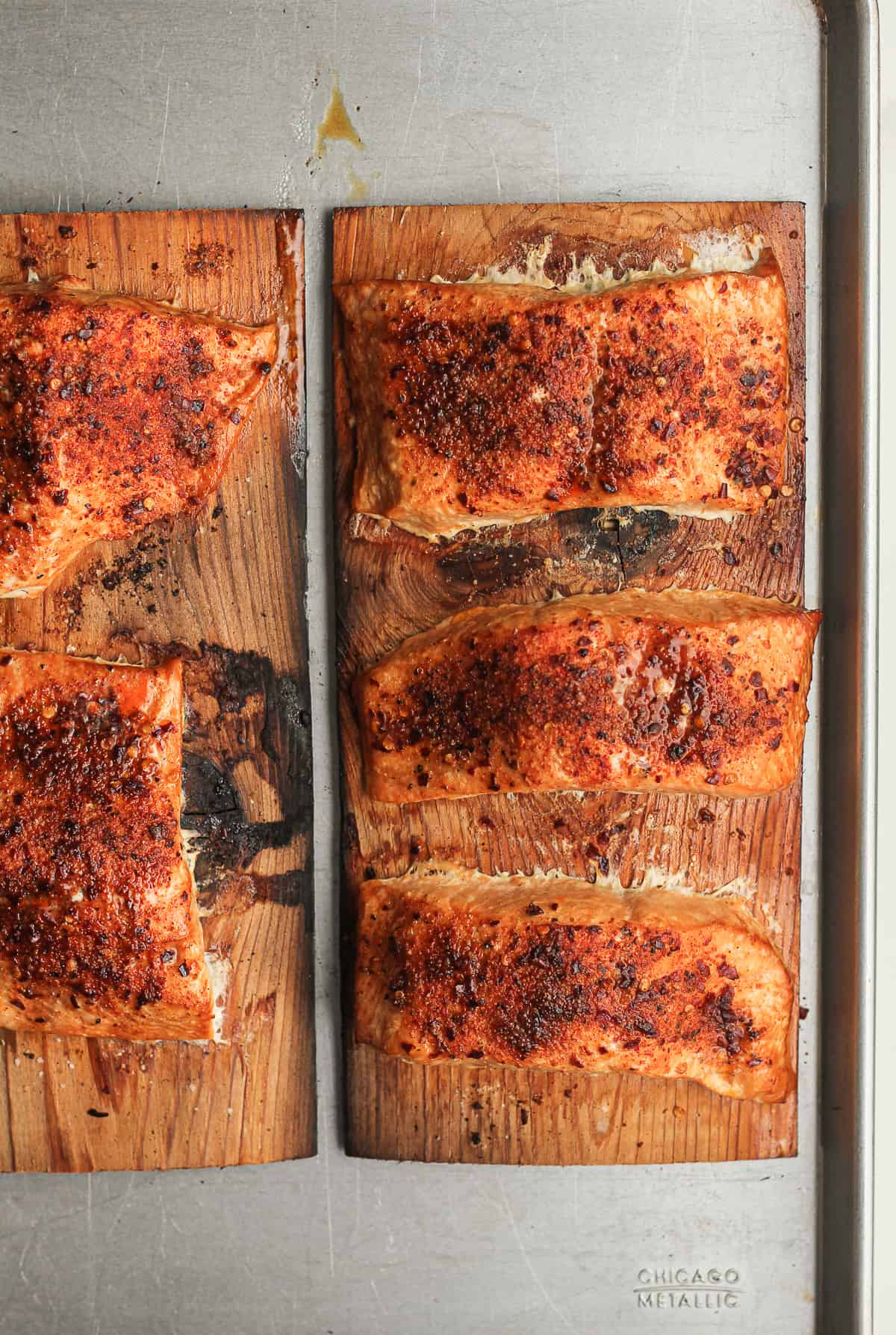 Two cedar planks with grilled salmon.