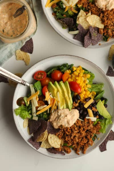 Overhead shot of taco salad with a jar of dressing.